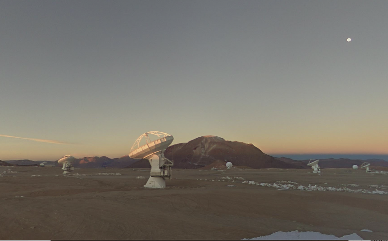 Twilight scene of dish-type radio telescopes on a high plain in the Chilean Andes.