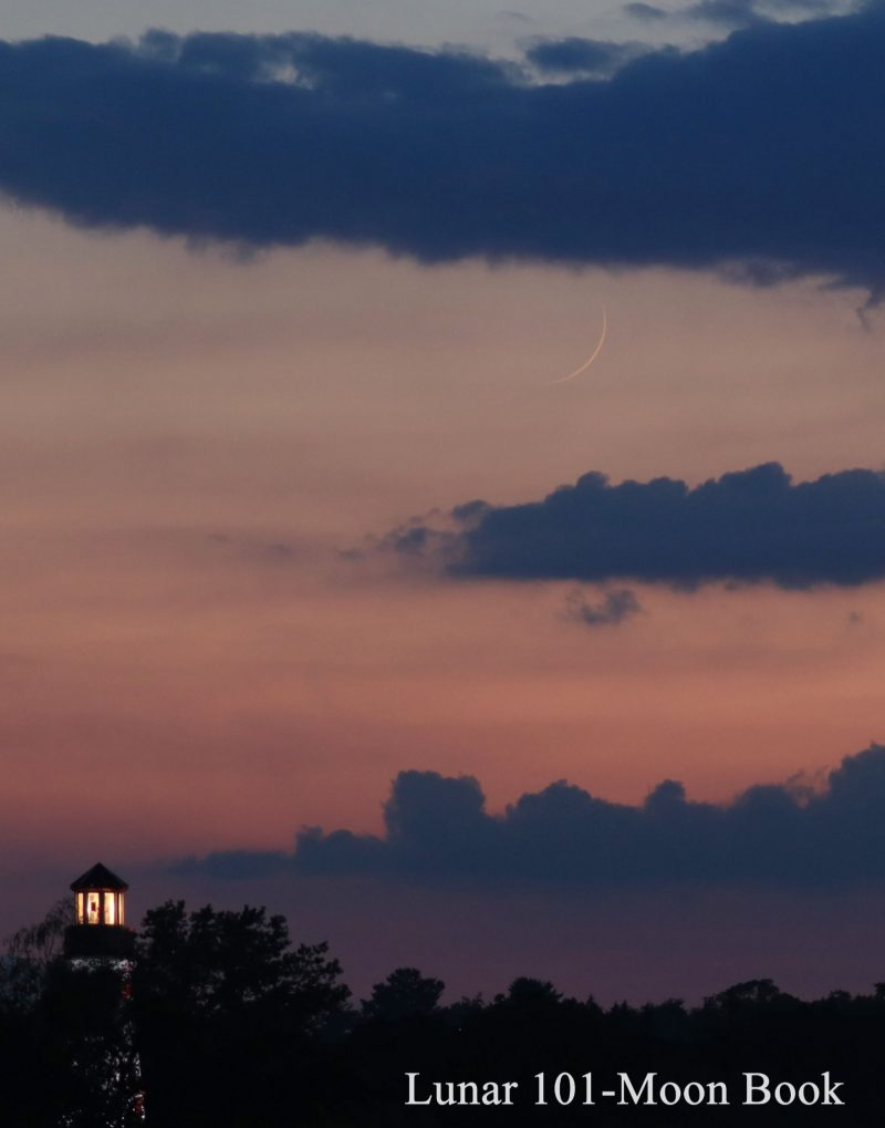 Very thin crescent moon in pink twilight sky with line of blue clouds below.