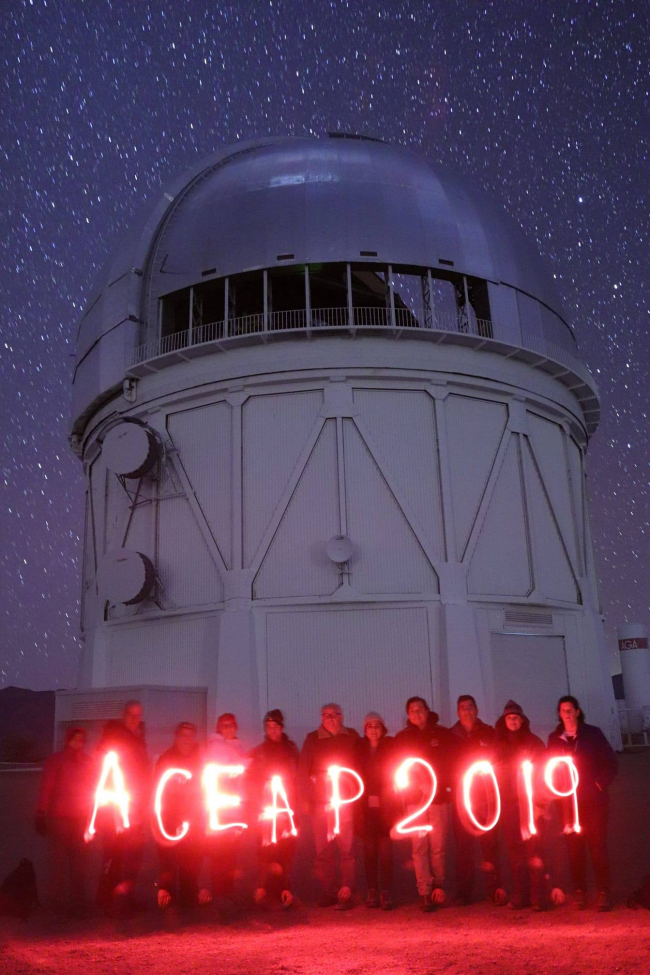 Nighttime: Large telescope dome with 15 people in front, holding a lighted sign reading ACEAP 2019.