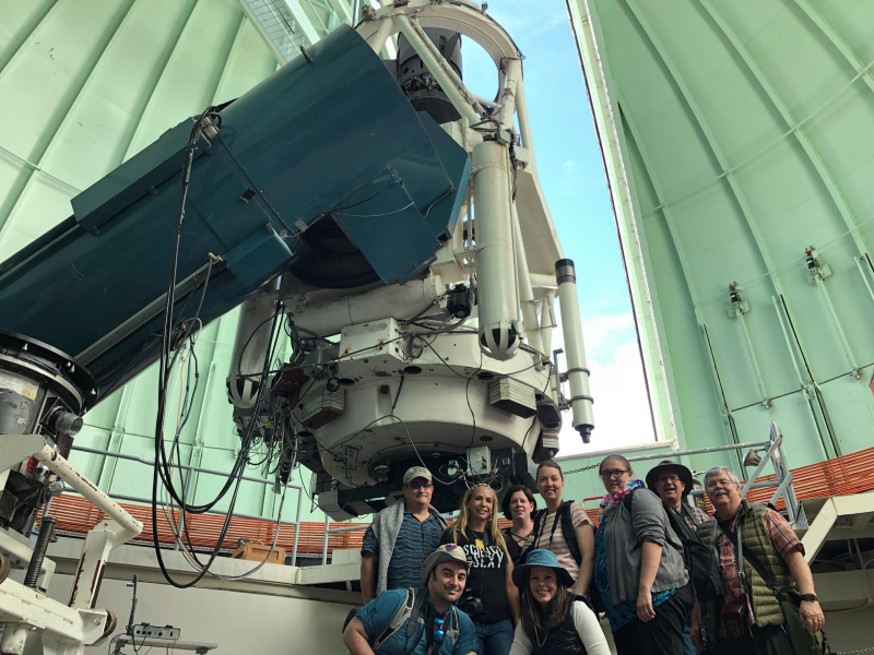 Group photo in front of large telescope, inside a large dome.