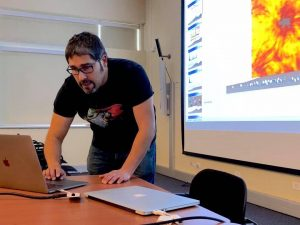 Man in a black t-shirt leaning over a laptop.