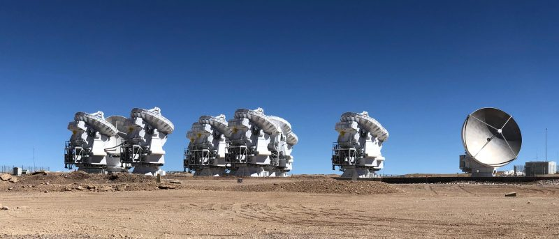 White radio telescopes with dishes on top above complicated machinery, under cobalt sky.