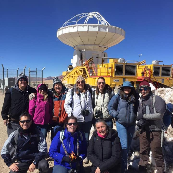 Ten people in coats posing in front of large radio telescope mounted on yellow transport vehicle.
