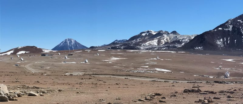 Scattered radiotelescope antennas on barren landscape, snow patches. Blue sky, distant mountains.