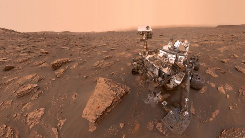 Complicated machine on wheels in a red-brown rocky landscape under a pale orange sky.
