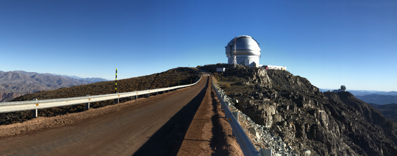 Looking along a road toward a large telescope dome, with a second dome in the distance.