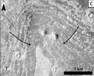 V-shaped area of concentric ridges peppered with craters and with two arrows marking locations.