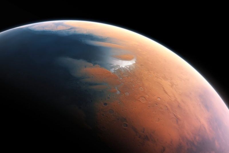 Orbital view of part of Mars with blue ocean to the left, the rest reddish tan with a few craters.