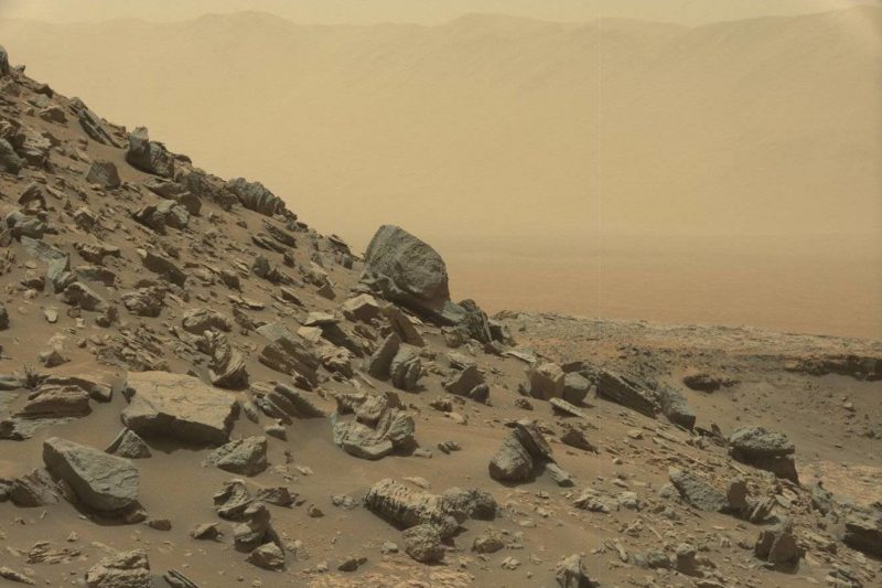 Rocks on a steep hillside on Mars under dull pink-yellow sky.
