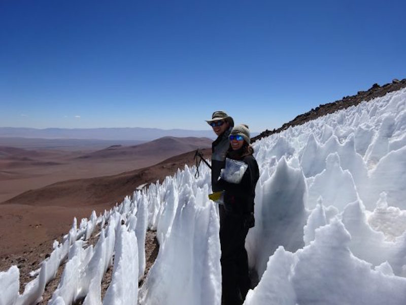 Man standing in field of waist-high pointy snow spikes on side of high mountain.