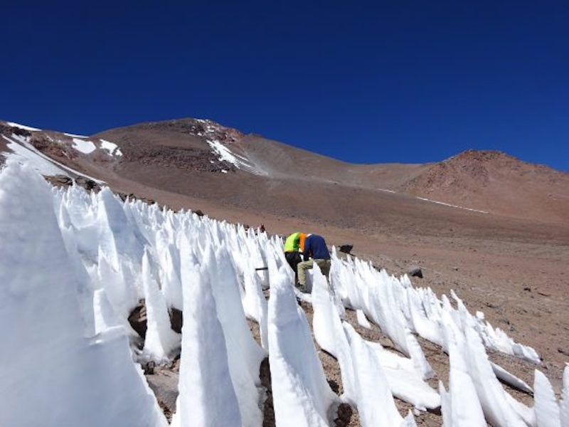 Very pointy ice cones on barren brown mountainside, cobalt blue sky.