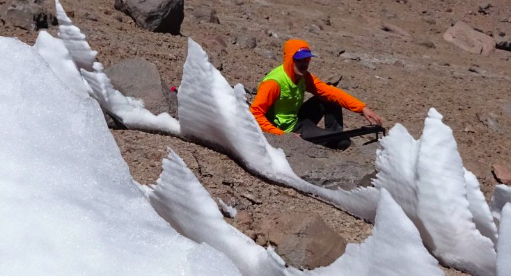 Blade-shaped snow spikes with warmly dressed scientist sitting nearby.