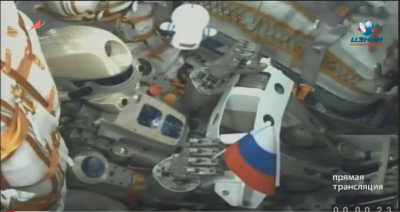 Jointed robot with camera face and human-like hands in a cramped space capsule.