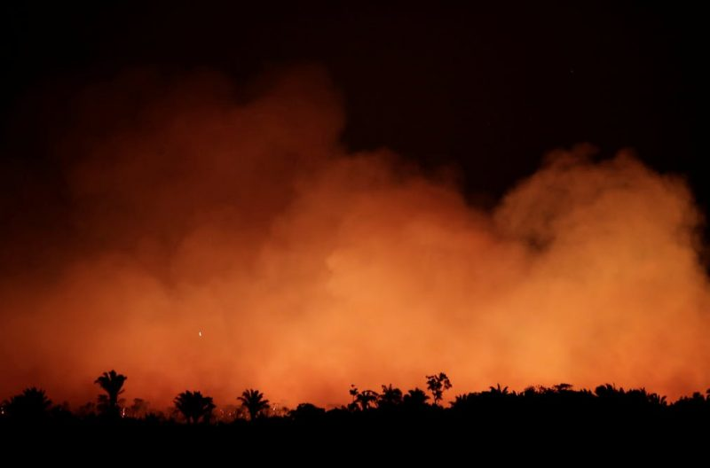 Huge billowing orange smoke clouds above silhouetted tropical forest.