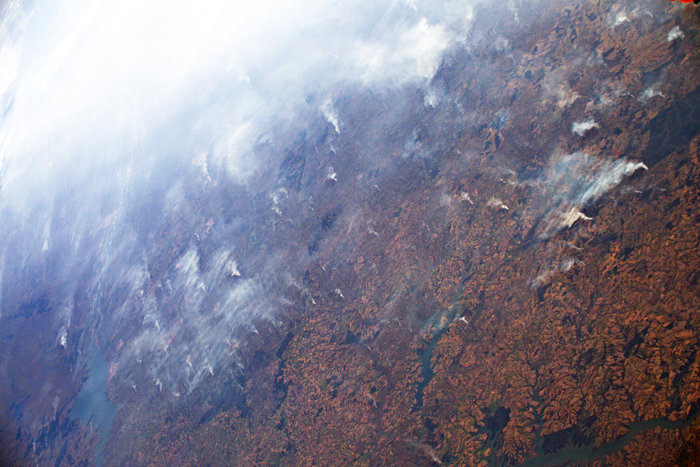 Orbital view of brown forest with rivers, half the area covered in white smoke.