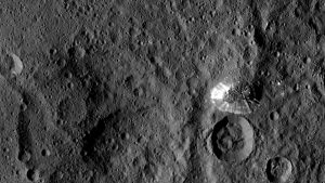 Rocky, moonlike planetary surface with large and small craters and a large cone-shaped mountain.