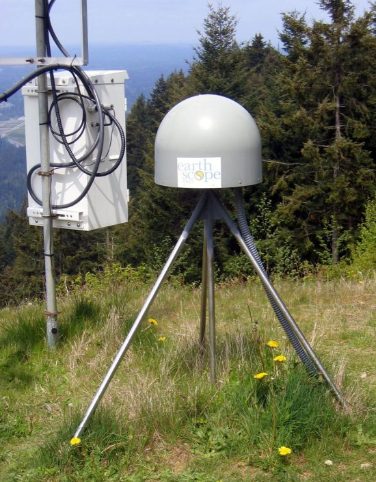 Metal dome on tripod of three short poles next to a metal box on a pole, in a field.