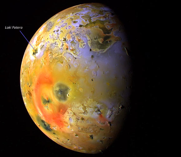 Jupiter's moon Io, close up, with Loki Patera indicated, many large and small bright-colored splotches.