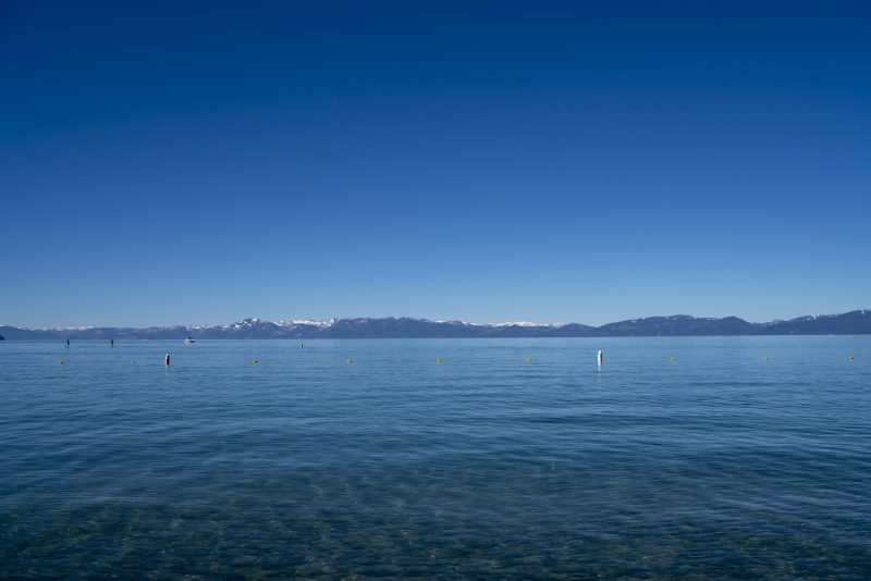 Slightly rippled blue water in wide lake, blue sky, very distant mountains.