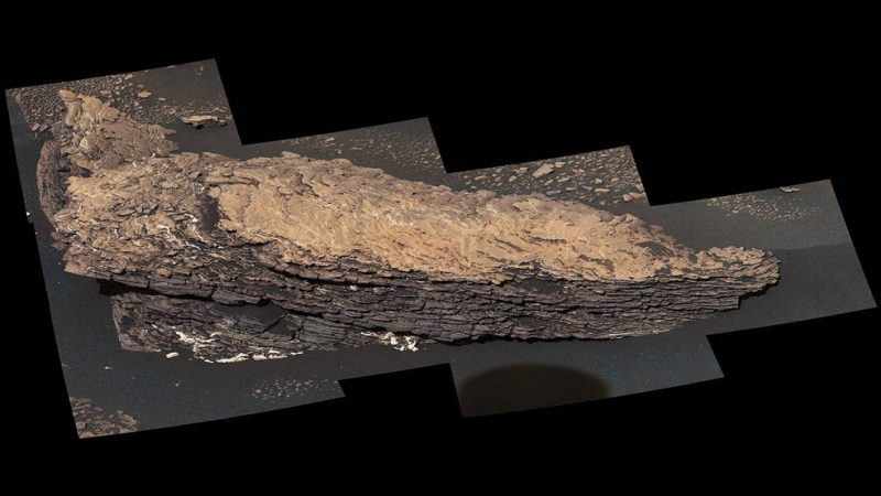 Many-layered, rough-looking, oblong tan rock with rough flat top.