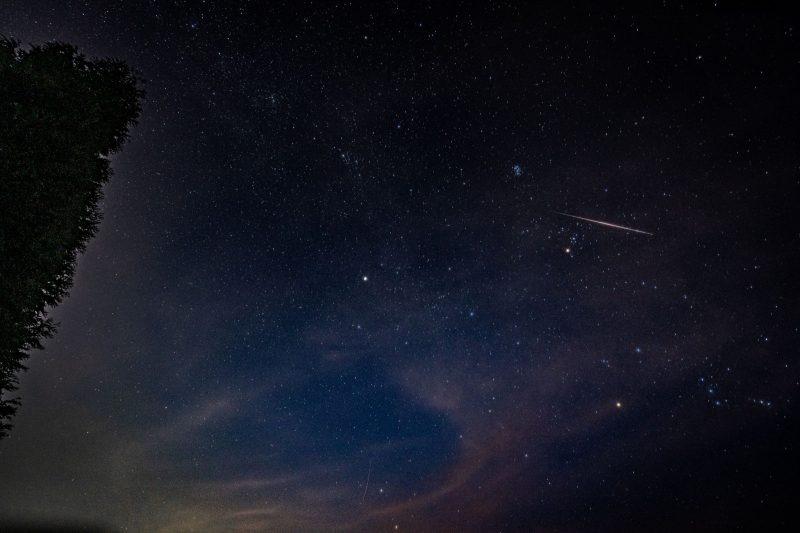 Meteor in a partly cloudy sky with some bright stars.