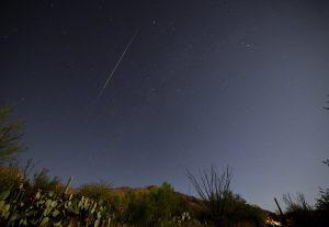 Bright, colorful meteor over desert landscape.