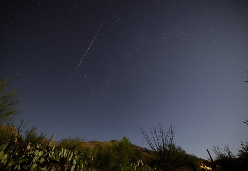 Long, bright, colorful meteor streaking over desert landscape.