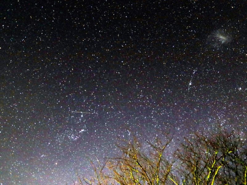 Meteor streaking across starry sky.