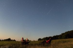 Two men sitting in camp chairs under a starry sky, with a meteor streaking past.
