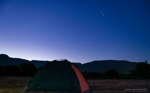 Bright meteor in a bluish sky, above a tent.