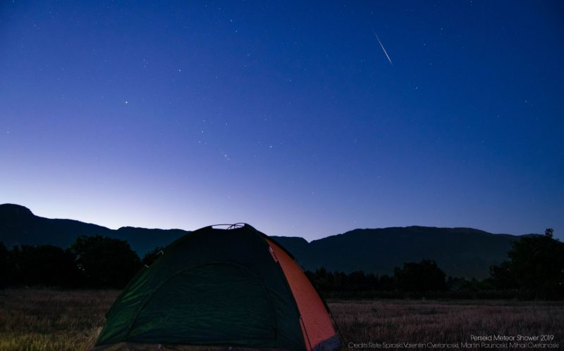 Bright meteor in a bluish sky, above a small dome-style tent and hilly horizon.