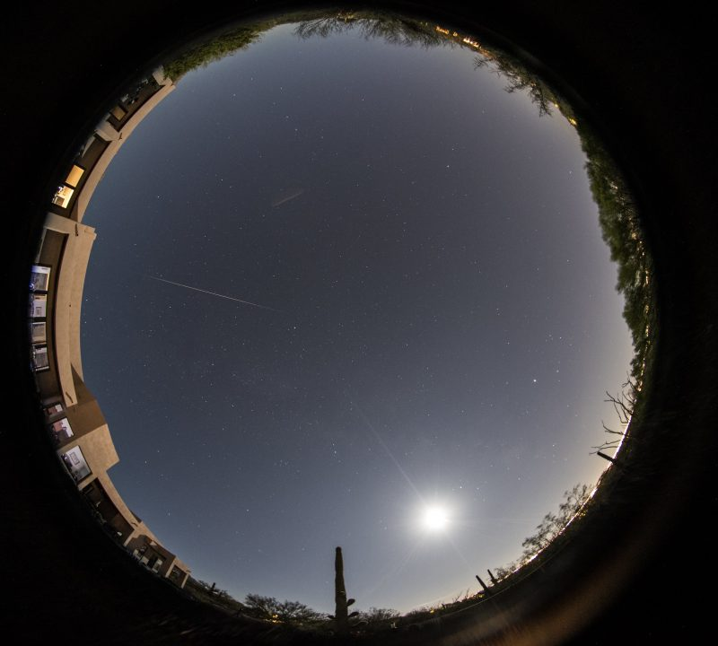 Circular all-sky view showing a bright meteor, with a bright moon nearby.