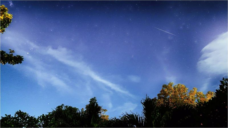 Bright meteor streaking along in a daytime-like bluish sky with some elongated white clouds.