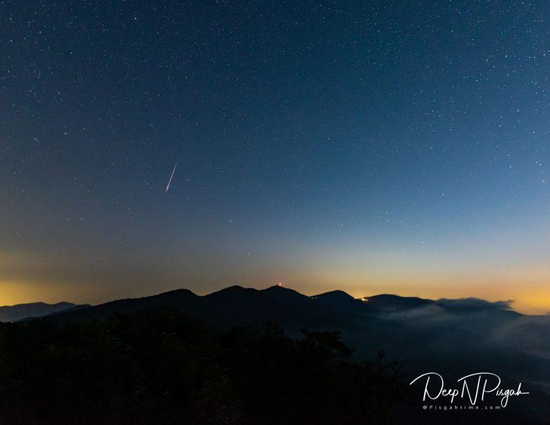 Meteor in darkening twilight sky over a mountain skyline.