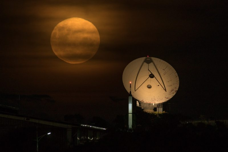 Large yellow full moon behind thin clouds next to a large round space tracking dish.