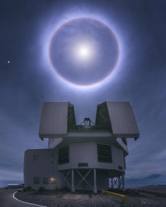 Bright moon halo above large, professional, open telescope dome.