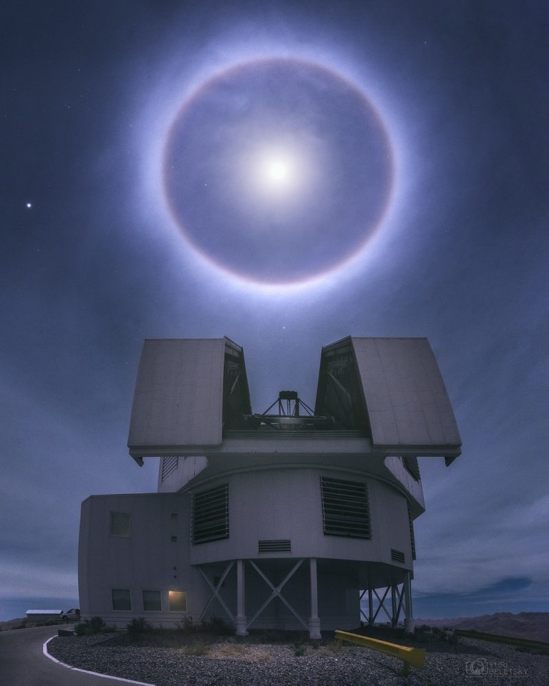 Bright moon halo surrounding fuzzy bright moon, above large, professional, open telescope dome.