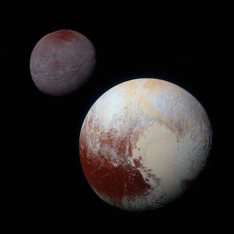 Pluto, with large tan and rust-colored areas, and smaller shadowy moon Charon in background.