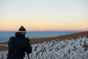 Self-portrait of photographer looking toward a field of ice structures, with Earth's shadow in the background.