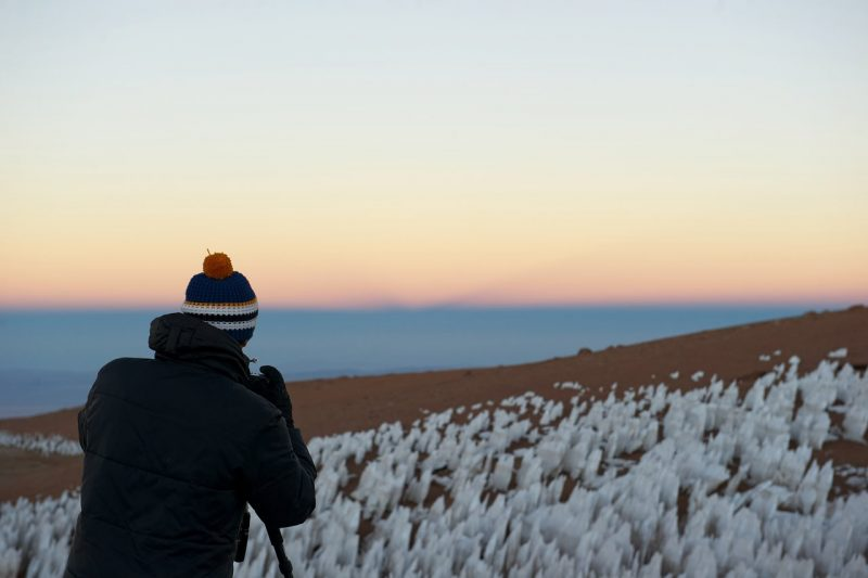 Photographer standing in a field of pointy ice structures, with darkness rising in sky over horizon.