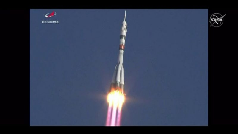 Soaring rocket with flame and smoke coming from first stage.