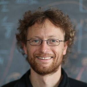 Youngish, red-curly-haired, bearded, smiling man with glasses.