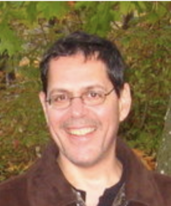 Smiling, middle-aged man in glasses.