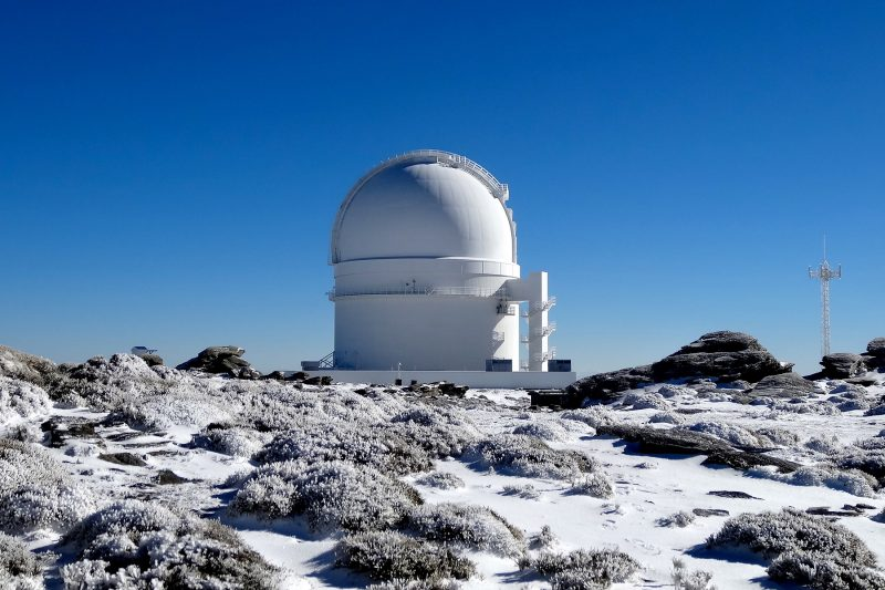 White-domed observatory on snowy, rocky mountain top.