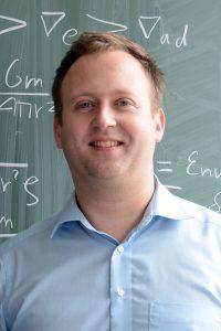 Smiling professor in front of blackboard.
