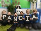 Schoolchildren holding letters spelling PANDIA