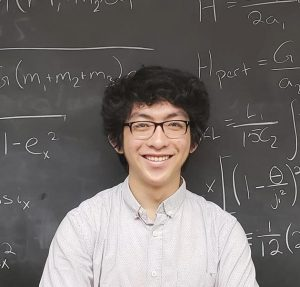 Young smiling professor in front of a blackboard.