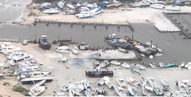 Ocean marina with very many destroyed boats washed up on the land.