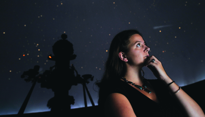 Young woman looking up at the stars in a planetarium.