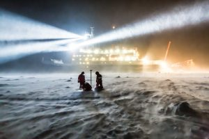 Scientists standing on sea ice, with the research ship Polarstern behind them, and a dark night sky above.
